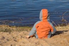 Le garçon s'assied sur la plage dans les regards de sable à la mer drapeau de concept de l'Ukraine et la nouvelle génération envi photographie stock