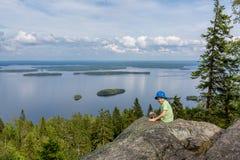 Le garçon s'assied sur la roche en Koli National Park Photo libre de droits