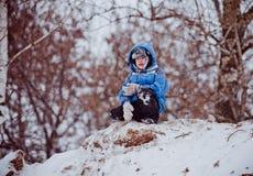 Le garçon s'assied sur le dessus de la colline Image stock