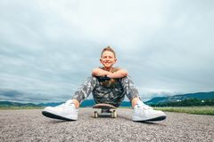 Le garçon s'assied sur le panneau de patin Photo stock