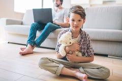 Le garçon s'assied sur le plancher avec ses jambes croisées Il tient l'ours blanc Le garçon regarde l'appareil-photo Son papa s'a images stock