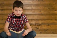 Le garçon s'assied sur le plancher lisant un livre sur le fond d'un mur en bois Image libre de droits