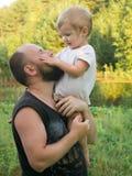 Le garçon s'assied sur son épaule du ` s de père photographie stock libre de droits