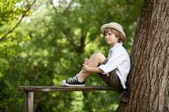 Le garçon s'assied sur un banc en bois Photos libres de droits