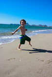 Le garçon sautant autour sur la plage Photographie stock