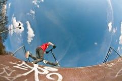 Le garçon sautant avec un scooter au-dessus d'une pipe photos stock