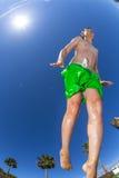 Le garçon sautant dans la piscine Photo stock
