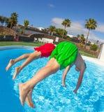 Le garçon sautant dans la piscine bleue Photo libre de droits