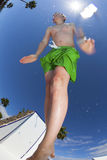 Le garçon sautant dans la piscine bleue Image libre de droits