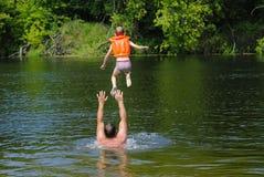 Le garçon sautant dans la rivière Photo stock