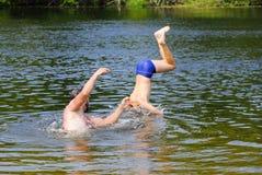 Le garçon sautant dans la rivière Photographie stock