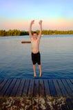 Le garçon sautant dans le lac Images libres de droits