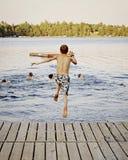 Le garçon sautant dans le lac Image stock