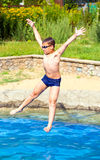 Le garçon sautant dans une piscine Images stock