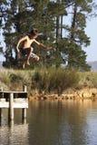 Le garçon sautant de la jetée dans le lac Photo stock