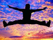 Le garçon sautant haut dans le ciel photos libres de droits