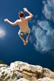 Le garçon sautant outre de la falaise dans l'eau bleue Photos stock