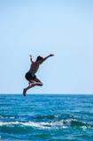 Le garçon sautant outre de la falaise dans la mer image libre de droits