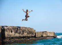 Le garçon sautant outre de la falaise dans la mer photographie stock libre de droits