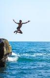 Le garçon sautant outre de la falaise dans la mer photo libre de droits