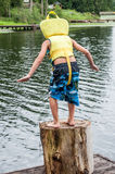 Le garçon sautant outre du dock Photos libres de droits
