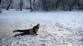 Le garçon sautant sur la neige et se couchent banque de vidéos