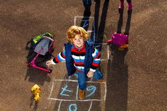 Le garçon sautant sur le jeu de jeu de marelle Image stock