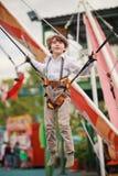 Le garçon sautant sur une attraction Images stock
