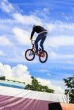 Le garçon sautant une haute stupéfient sur un vélo de montagne Le jeune cavalier à la roue de son bmx fait un tour Tours de cycli Photographie stock