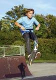 Le garçon saute avec le scooter au parc de patin au-dessus d'une rampe Images libres de droits