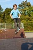 Le garçon saute avec le scooter au stationnement de patin Photographie stock libre de droits