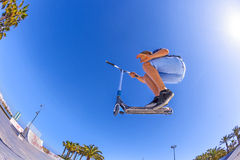 Le garçon saute avec son scooter à un parc de patin Photo libre de droits