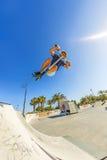 Le garçon saute avec son scooter à un parc de patin Photo stock