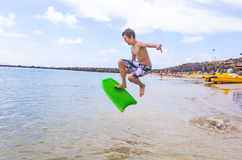 Le garçon saute dans l'océan avec son conseil de boogie Images libres de droits