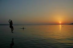 Le garçon saute dans le coucher du soleil de bord de la mer de Starigrad-Paklenica de mer Image libre de droits