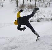 Le garçon saute dans une congère photographie stock libre de droits