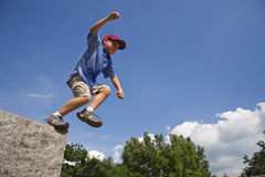 Le garçon saute de la roche. image stock