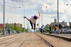 Le garçon saute la culbute à l'envers sur des voies de tramway dans la ville Images stock