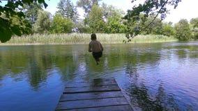 Le garçon sautent à la rivière du pilier banque de vidéos