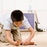Le garçon se mettant à genoux et remontant partie d'un mode Image libre de droits