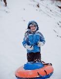 Le garçon se tenant dans la neige et garde la tuyauterie Photos libres de droits