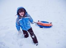 Le garçon se tenant dans la neige, tenant la tuyauterie Photos libres de droits