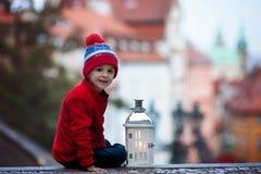 Le garçon, se tenant sur des escaliers, tenant l'ours de lanterne et de nounours, regardent o Image libre de droits