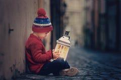 Le garçon, se tenant sur des escaliers, tenant l'ours de lanterne et de nounours, regardent o Images stock