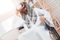 Le garçon se tient derrière un homme arabe dans un fauteuil roulant qui regarde dans des verres de réalité virtuelle image libre de droits