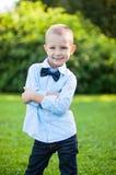 Le garçon se tient en parc sur un fond vert Photos libres de droits