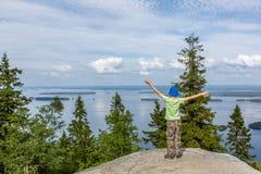 Le garçon se tient sur la roche en Koli National Park Photo libre de droits