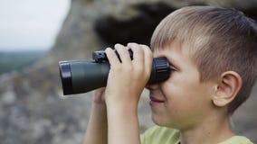 Le garçon se tient sur le dessus de la montagne et regarde les jumelles clips vidéos
