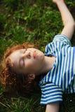 Le garçon se trouve sur la terre ayant étiré des mains dans les parties Photographie stock libre de droits
