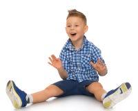 Le garçon se trouve sur le plancher Photographie stock libre de droits